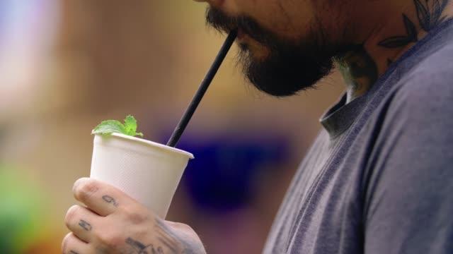 stockvideo's en b-roll-footage met aziatische hipster man drinken whisky met papieren beker en stro in een stedelijke omgeving - stro