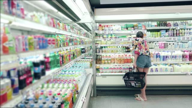 asian hipster woman in grocery store - замороженные продукты стоковые видео и кадры b-roll