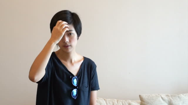 Asian hipster woman setting her hair and wearing sunglasses video