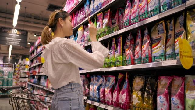 asian hoarder woman shopping in supermarket - замороженные продукты стоковые видео и кадры b-roll