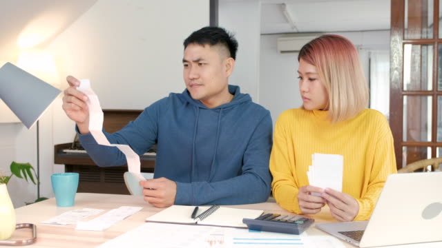 Asian husband got long payment bill and upset on home budget on laptop with wife at living room in home