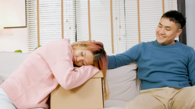 Video asian husband wake up wife from resting on cardboard box while moving to new house.