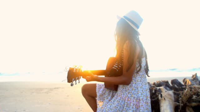 Asian Indian girl in Retro sundress playing guitar Smiling young Asian Indian girl in Retro style sundress playing the guitar on the beach sun flare boho stock videos & royalty-free footage