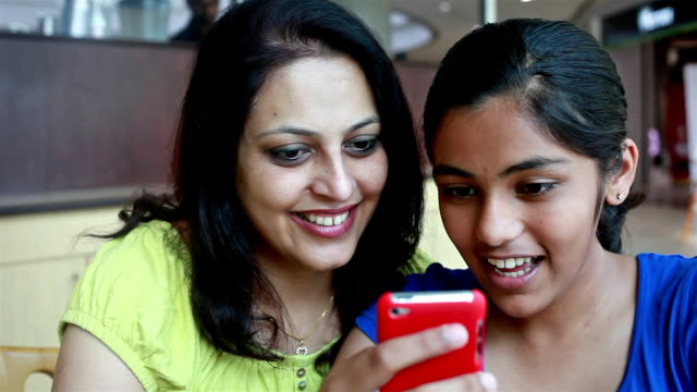 Asian Indian Mother and Daughter using Phone reading SMS video