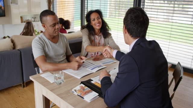 Agente de seguros asiático, agitando as mãos com um casal em uma reunião em sua casa - vídeo