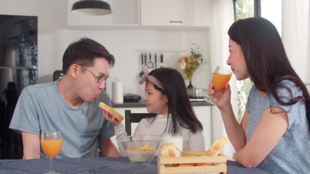 アジア系の日本人家族は自宅で朝食をとります。アジアのお母さん、お父さん、娘は、朝、台所のテーブルの上のボウルにパン、コーンフレークシリアル、ミルクを食べて幸せな話をしてい� - 母娘 笑顔 日本人点の映像素材/bロール