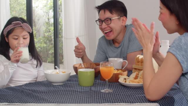 アジア系の日本人家族は自宅で朝食をとります。アジアのお母さん、お父さん、娘は朝、台所のテーブルの上のボウルにパン、トウモロコシフレークシリアル、ミルクを食べながら、一緒に� - 母娘 笑顔 日本人点の映像素材/bロール