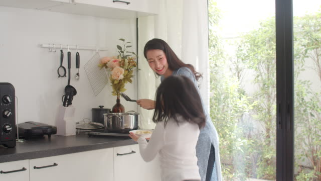 Asian Japanese Mom and Daughter cooking at home. Lifestyle women happy making pasta and spaghetti together for breakfast meal in the kitchen at home. Slow motion shot.