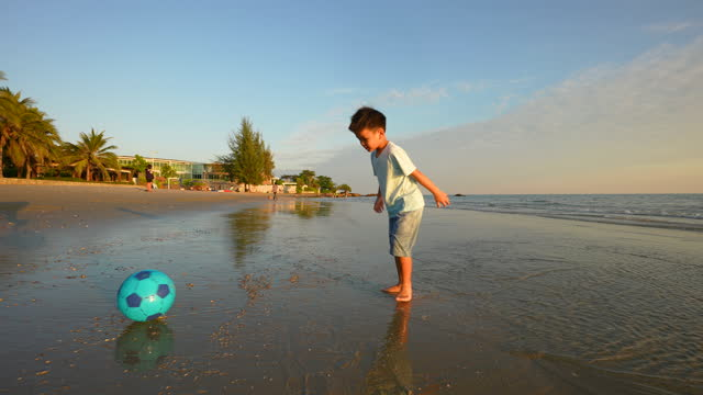 Asian kid play football at the beach. Concept of vacation and healthy