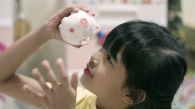 vidéos et rushes de gosse asiatique essayant d'obtenir l'argent de la tirelire - tirelire