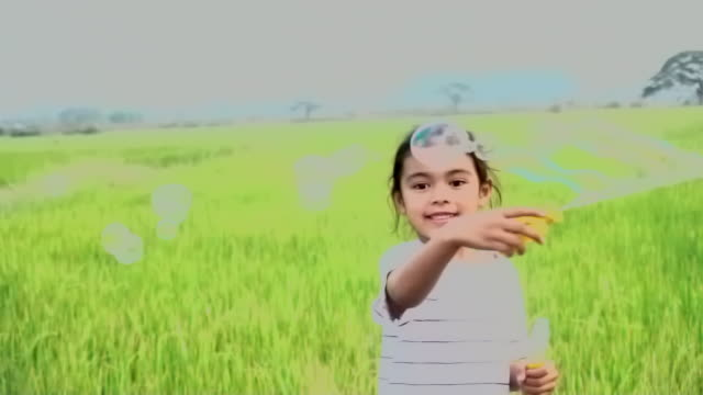 Asian kids laughing and having fun in a summer green paddy field blowing bubbles, with slow motion - vídeo