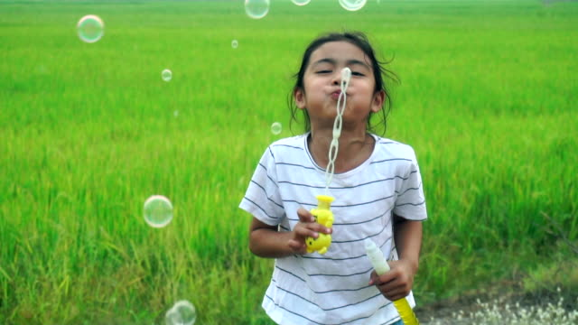 Asian kids laughing and having fun in a summer green paddy field blowing bubbles. - vídeo