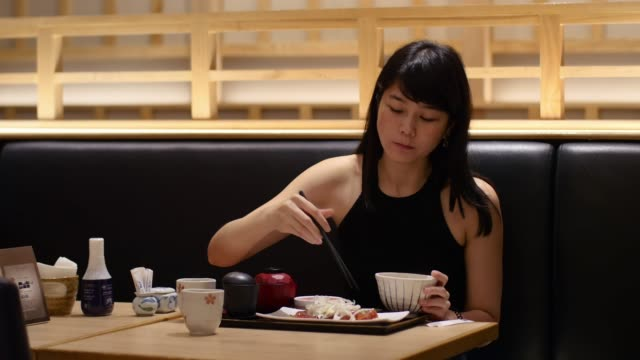 asian lady eating Zuke Maguro fresh tuna sashimi japansese dish using chopstick video