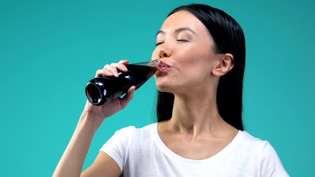 asiatische dame genießen sie süße kohlensäurehaltige getränk, kaltes getränk, blauer hintergrund - alkoholfreies getränk stock-videos und b-roll-filmmaterial