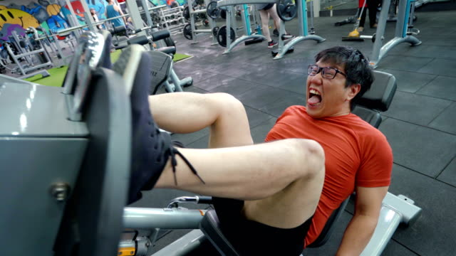 Asian large build man exercising his leg with extremely painful face.