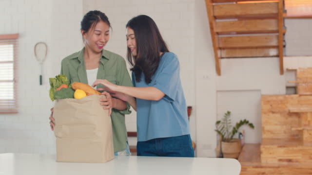 Asian Lesbian couple hold grocery shopping paper bags from supermarket put it in kitchen at home.