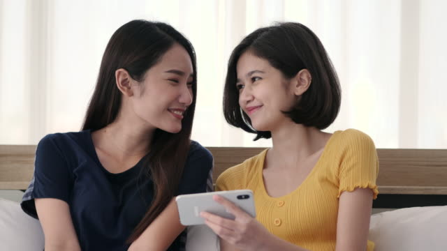 Asian lesbian couple surfing the net with smart phone