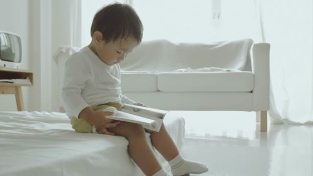 Asian little boy reading a book on the bed video