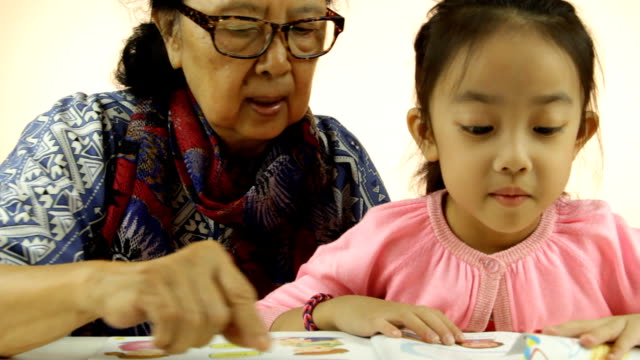 Asian little girl and grandma reading book video