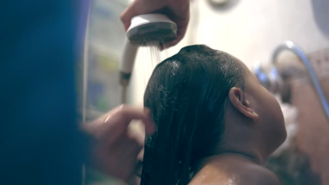 Asian little girl bathing and washing hair by her mother
