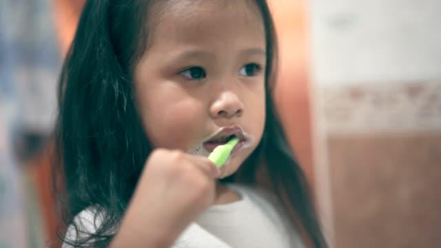 stockvideo's en b-roll-footage met aziatisch meisje borstelen haar tanden en tong - tong mond