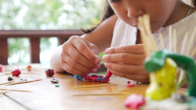 vídeos de stock, filmes e b-roll de menina asiática concentrada com massinha de modelar o barro na intenção. vídeo gravado em 60fps - arte e artesanato assunto
