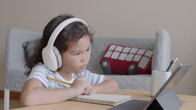 ragazza asiatica che fa i compiti e impara online tramite comunicazione internet con cuffia su tablet a casa del mattino - didattica a distanza video stock e b–roll