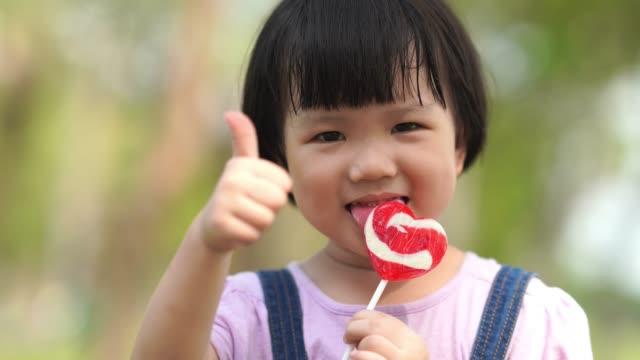 亞洲小女孩吃棒棒糖, 豎起大拇指 - 波板糖 個影片檔及 b 捲影像