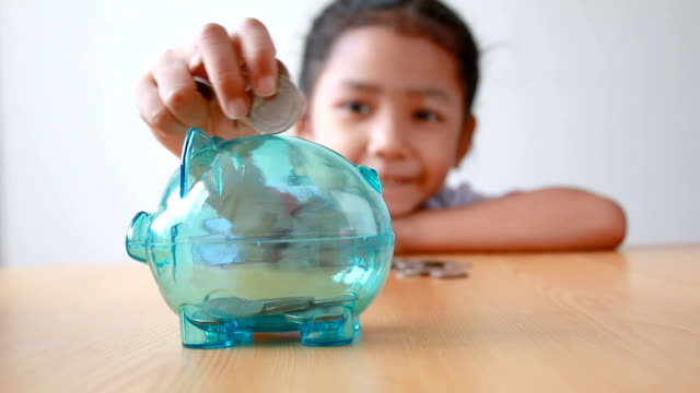 Asian little girl in Thai kindergarten student uniform putting money coin into clear piggy bank select focus on pig saving money for education concept Asian little girl in Thai kindergarten student uniform putting money coin into clear piggy bank select focus on pig saving money for education concept piggy bank stock videos & royalty-free footage