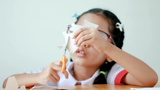 asian little girl in thai kindergarten student uniform using scissor to cut the white paper making family shape father mother son and daughter on wooden table select focus on hands - forbici video stock e b–roll