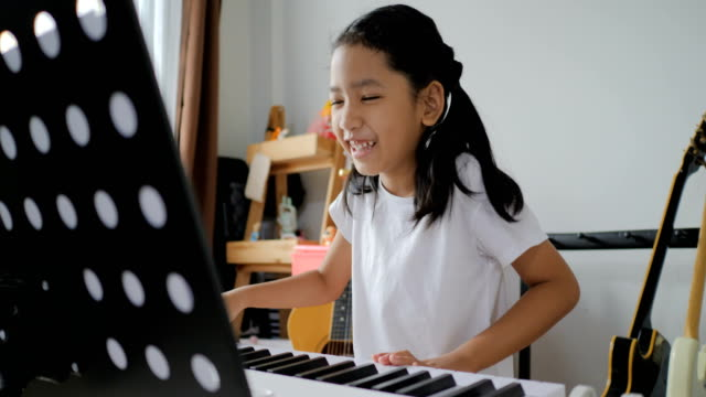 vídeos de stock e filmes b-roll de asian little girl learning to play basic piano by using electric synthesizer keyboard for beginner music instrumental self studying at home - piano