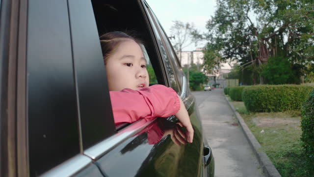 4K Asian little girl looking something out the car. In the morning, the girl was looking at something outside the car window on the way to school. children relax with street view from the car. Family at car concept.