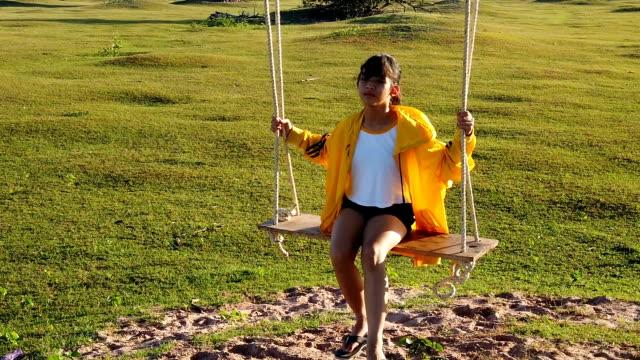 asian little girl on wooden swing