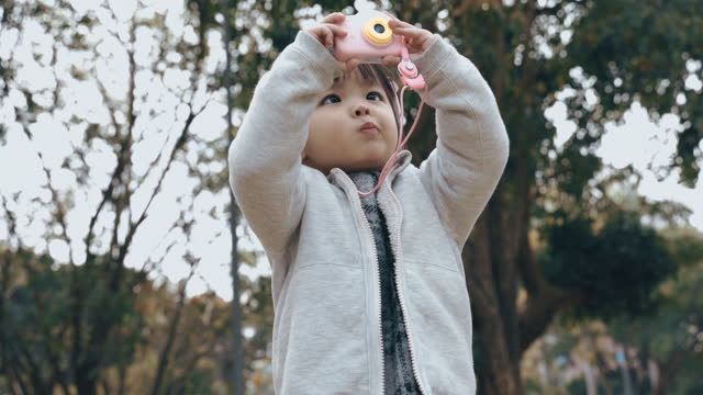 Asian little girl playing with toy camera in the park
