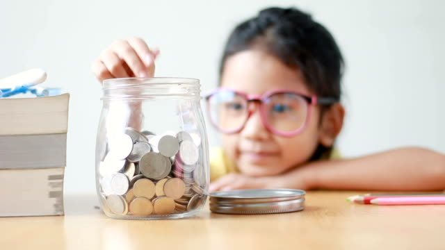 asian little girl putting the coin into a  clear glass jar on table metaphor saving money concept with sound select focus on jar - frugal lifestyle stock videos and b-roll footage