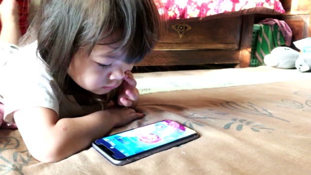 Asian little girl watching and playing smartphone video