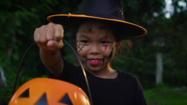 Asian little girl with a painted face is showing a pumpkin toy in halloween