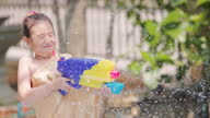 istock Asian little girl with traditional thai dress playing water gun in the water pool at summer time 1313237396