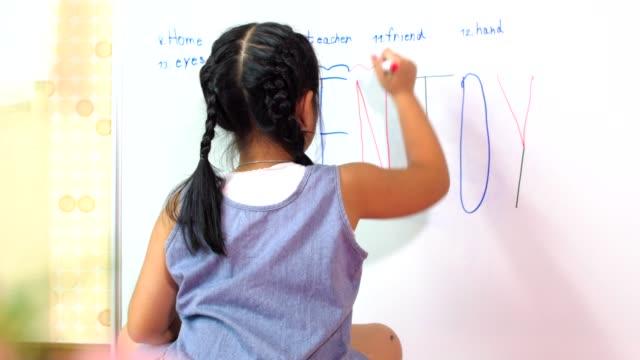 Petite asiat écrit à bord de la salle blanche de classe, le concept de l'éducation - Vidéo
