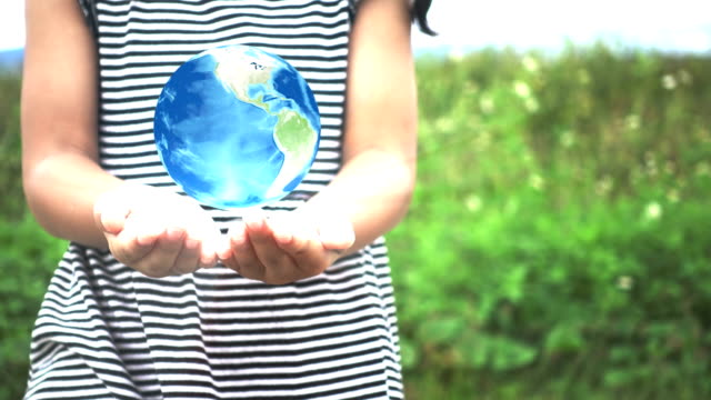 Asian little girl's hands holding spinning globe at outside. video