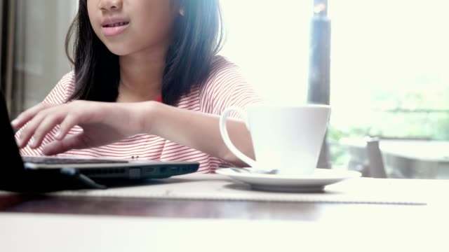 Asian little girls playing laptop, drinking hot milk at table in cafe.