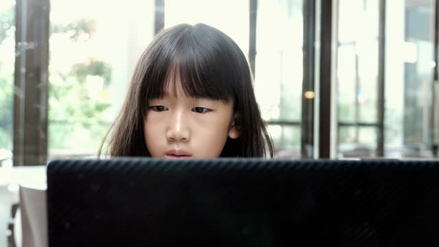 Asian little girls playing laptop in cafe.