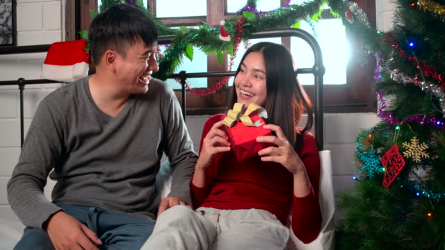 Asian Lovers Couples give gifts at christmas In the bedroom In a white apartment