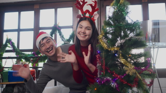 Asian Lovers helping each other decorate the Christmas tree In the bedroom In a white apartment