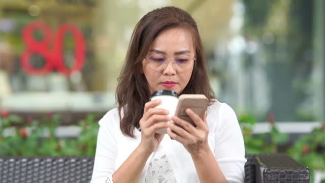 asiatischer luxus reife frau mit smartphone und trinken heißen kaffee vom take away cup - online dating stock-videos und b-roll-filmmaterial