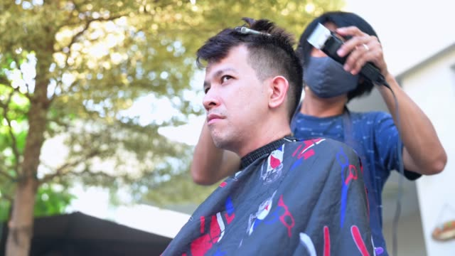 vídeos de stock e filmes b-roll de asian making haircut at home garden. learning online barber courses during lockdown for new occupation. new normal life after covid-19 outbreak pandemic situation. - covid hair