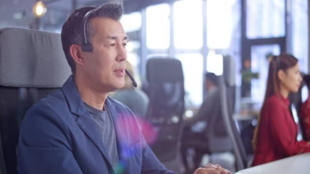 近代的なオフィスでコールを管理するdsアジアの男性コールセンターエージェント - オペレーター 日本人点の映像素材/bロール