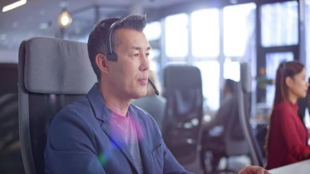 近代的なオフィスで彼のワークステーションでプロの顧客サービスを提供するdsアジアの男性コールセンターエージェント - ビジネスマン 日本人点の映像素材/bロール