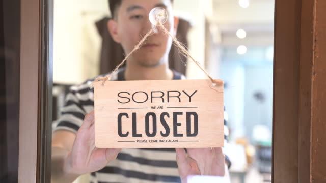 stockvideo's en b-roll-footage met aziatische mannelijke werknemer die plaats met tablet sluit - recessie