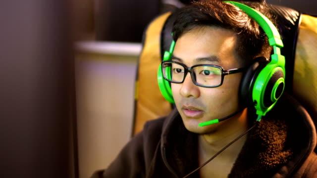cu アジア男性ゲーマーのマイクを使って緑のヘッドセットでゲームをプレイ - ゲーム ヘッドフォン点の映像素材/bロール